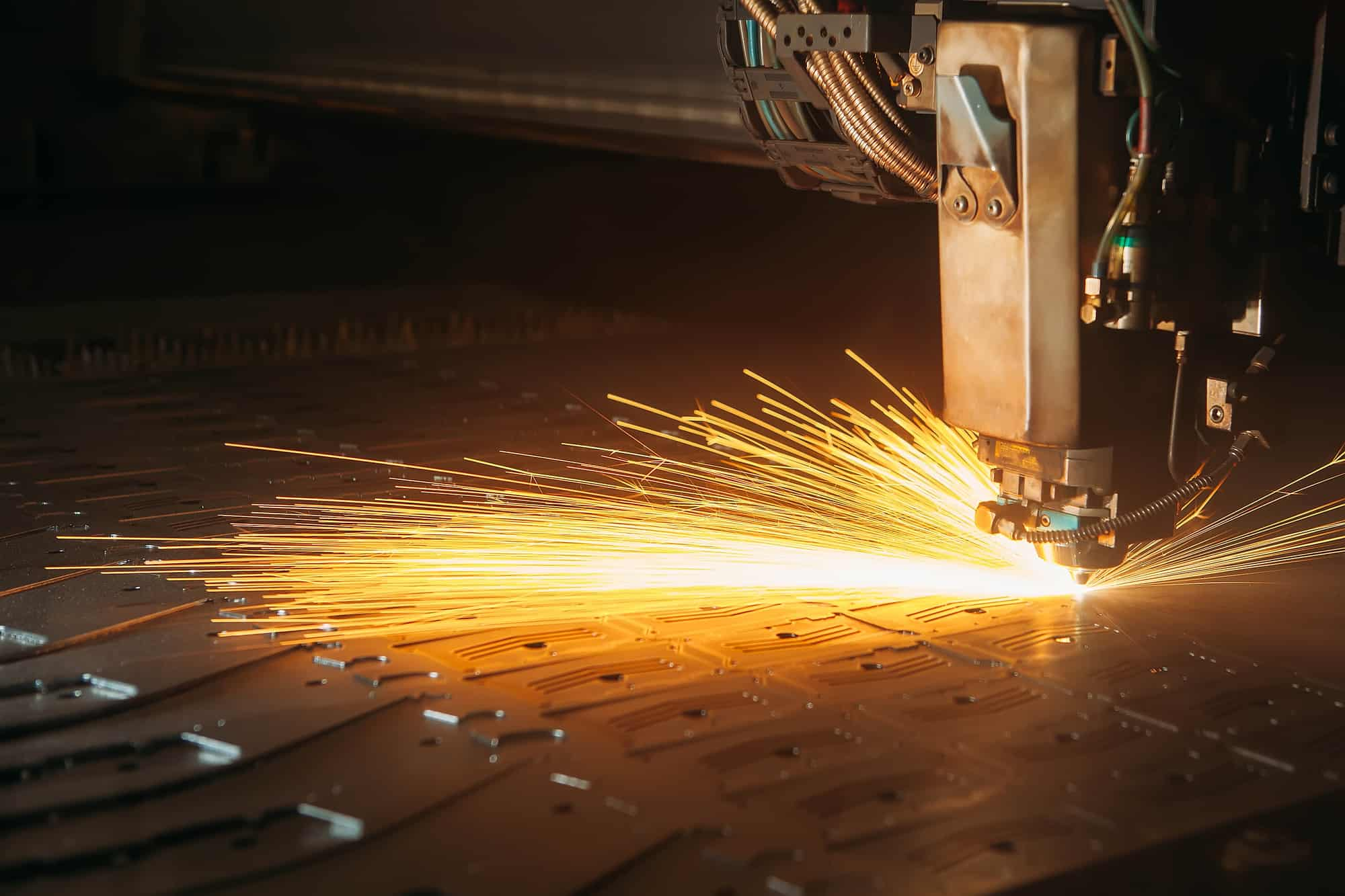 Laser cutting machine cuts the metal with sparks industry 4.0