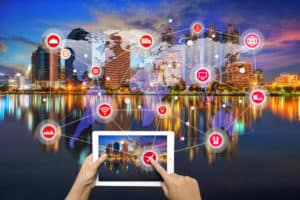 Tablet connected to city with IOT icons